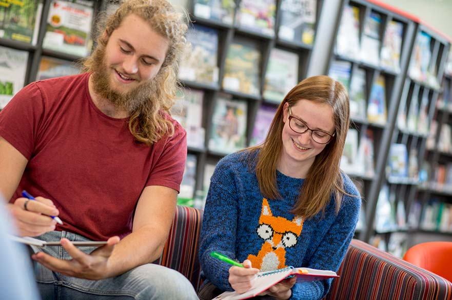 students sat on sofa in library writing in notebooks